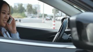 Tracking shot of young Asian female driver sitting in car and talking on cell phone while staying in parking lot