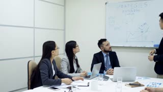 Tracking shot of young Asian man in formalwear standing at whiteboard and presenting business strategy to group of partners