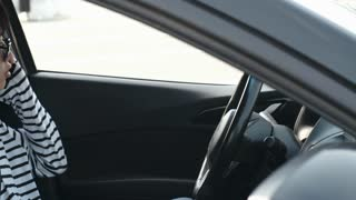 Tracking shot of young Asian man in sunglasses sitting in car in driver seat and talking on cell phone