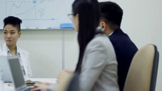 Tracking shot of young Asian woman talking to employees when discussing corporate strategy at meeting in conference room