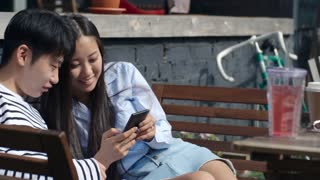 Tracking shot of young Asian woman watching something on smartphone with boyfriend and laughing while sitting outdoors on bench