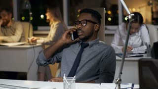 Tracking shot of young black man in glasses and necktie talking on the phone when sitting at office desk, his colleagues working in the background