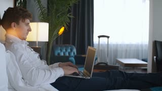 Tracking shot of young businessman reading something on laptop screen and drinking coffee on comfortable bed in modern hotel room
