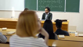 Tracking shot of young female student discussing topic with university professor when having lecture with multi ethnic groupmates