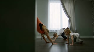 Tracking shot of young mother in sportswear teaching downward-facing dog pose to little children while practicing yoga with them in morning