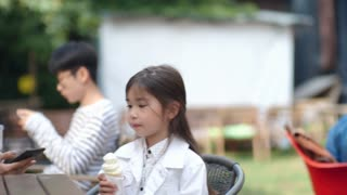 Tracking shot of young pretty Asian woman taking selfie with cute little girl posing with ice cream at smartphone camera in outdoor cafe