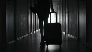 Tracking with low-section of silhouette of elegant woman in skirt and high heels shoes carrying suitcase and walking along hallway of hotel towards her room; black and white slow motion shot