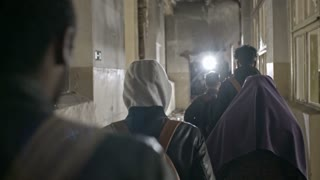 Tracking with rear view of male Arab refugees walking along hallway of destroyed building; Muslim woman in niqab taking child from hands of soldiers in uniform passing firearms through broken window