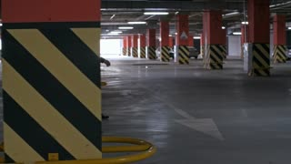 Tracking with side view of African businessman in suit and his Caucasian colleagues with briefcases talking and walking through dark underground parking lot