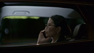 Tracking with side view of Asian businesswoman in glasses calling business partner on mobile phone while seating in backseat of car driving through city at night