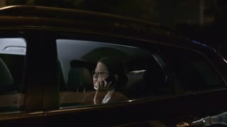 Tracking with side view of Asian businesswoman in glasses riding in backseat of car and talking on mobile phone
