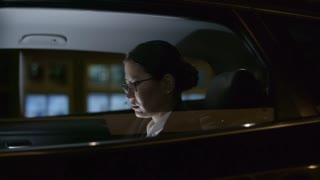 Tracking with side view of Asian businesswoman in glasses riding in backseat of taxi at night
