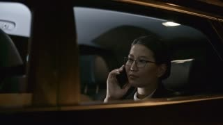 Tracking with side view of Asian businesswoman in glasses talking on mobile phone while riding in backseat of moving car at night