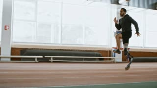 Tracking with side view of determined sportsman with prosthetic fitness leg warming up and running on indoor track