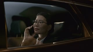 Tracking with slowmo of Asian businesswoman in sitting in backseat of moving car and chatting on mobile phone