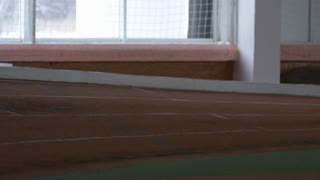 Tracking with slowmo of disabled athlete with prosthetic running leg sprinting on track in indoor stadium
