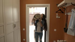 Tracking with slowmo of excited Asian couple carrying rolled up carpet and walking into their new house, then hugging and smiling with happiness