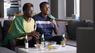Two African-American men sitting on couch at home, watching soccer game on TV, raising flag of Brazil and jumping up with excitement while celebrating goal