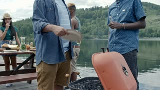Two black men standing by lake, talking, drinking from transparent bottles and waiting for meat to grill, one blowing extra air to grill with plastic plate, their friends standing in the background