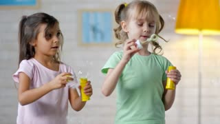 Two cute girls of primary school age standing next to each other and blowing soap bubbles with bubble wands