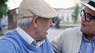 Two elderly male friends meeting each other in pedestrian street after long time, talking and smiling