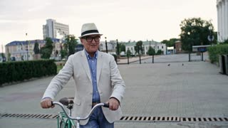 Two elderly male friends, one with walking stick and one with bicycle, meeting each other in the city and then going for walk