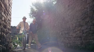 Two elderly male friends, one with walking stick and one with bicycle, walking in narrow way between old stone buildings