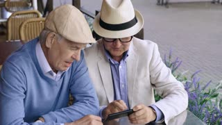Two elderly men sitting at table in street cafe and talking self portrait together on smartphone, then viewing it