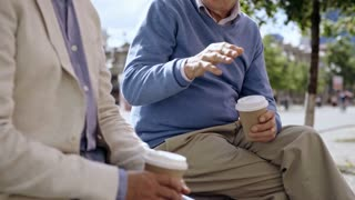 Two elderly men sitting on bench in pedestrian street, holding take away coffee mugs and talking to each other