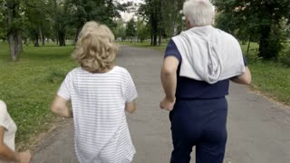 Two elderly people jogging in park when four more seniors join them waving hands and greeting each other, follow shot, rear view