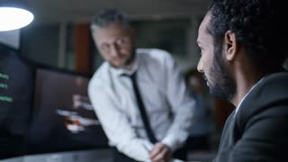 Two experienced computer programmers discussing code on computer monitor while working late in the office