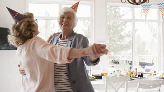 Two joyous senior women smiling and dancing together in the living room while having birthday party with friends; elderly couple dancing in background