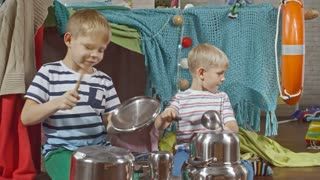 Two little brothers sitting on floor in kid's room and using metal pots and spatulas while imitating playing drums