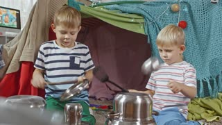Two little brothers sitting on floor in kids room with handmade play tent and using metal pots, ladle and spatulas while imitating playing drums