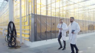 Two middle aged men in lab coats walking along industrial greenhouse complex hallway and discussing plant growing