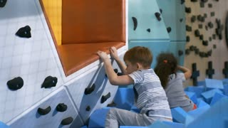 Two multi ethnic children, boy and girl, playing on climbing wall with cube pit when spending time in indoor amusement park