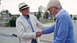 Two senior male friends shaking hands when meeting each other in the city, one of them showing his bicycle to the other one