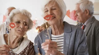 Two senior women holding lips on a stick and sparklers while hiving fun at birthday party with friends