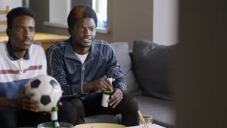 Two young African-American men sitting on couch in the living room, watching soccer match on TV, cheering team and celebrating goal with beer