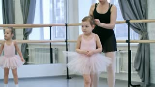 Unrecognizable female ballet teacher taking shy little girl to her first lesson, other girls jumping around the room