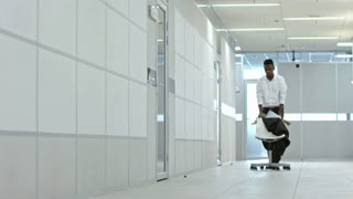 Upset african american businessman pushing chair with his belongings through hallway in office center while getting fired