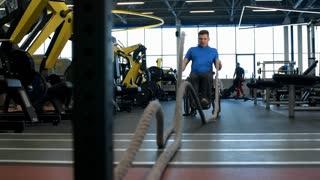 Slow motion shot of paraplegic man in wheelchair doing battle ropes workout
