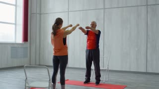 PAN with slowmo of young female fitness instructor and senior man in sportswear standing facing each other and doing warming up exercise for wrists while training in fitness studio