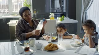 PAN of busy black mother talking on phone and pouring milk into glass for preschool age girl eating breakfast at kitchen table