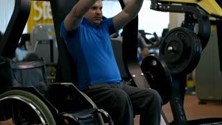 Tilt up of paraplegic man breathing hard and training on chest press machine in gym; wheelchair standing beside him