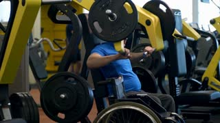 PAN of disabled sportsman exercising on chest press machine in gym; wheelchair standing beside him