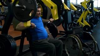 PAN of paraplegic man training on chest press machine in gym and breathing hard; empty wheelchair standing beside