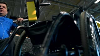 Low angle shot with PAN of determined paraplegic man listening to music in earphones and training on chest press machine in gym; empty wheelchair standing beside