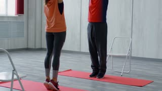 Tilt up of female yoga instructor in sportswear and senior man with grey hair and moustache standing on tiptoes and stretching their arms in fitness studio