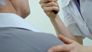 Tilt up of female eye care professional using retinoscope while examining eyes of senior man during medical checkup